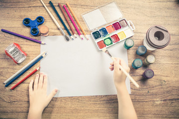 Cute child paints with colored pencils on paper top view