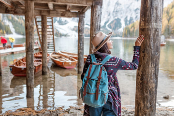 Asian girl traveler at the majestic Braies lake in South Tyrol, Italy. Vacation and adventure outdoors in nature park concept