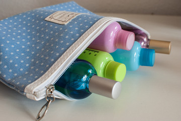 Blue travel toiletry bag with travel toiletries, small plastic bottles of hygiene products and perfume.