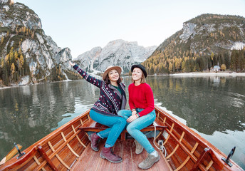Two happy woman friends on the boat or canoe cruise tour on lago Di Braies lake in Italian Dolomites Alps