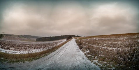 Panorama of the field in the fall. Arable land covered with snow