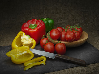 Sweet peppers and red tomatoes, still life. Light painting. With retro knife and slate rustic background.
