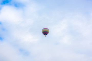 Hot air balloons fly over the sky.