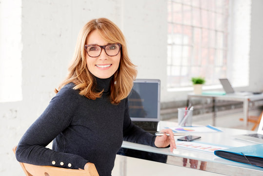 Confident businesswoman wearing casual clothes while sitting at office and working
