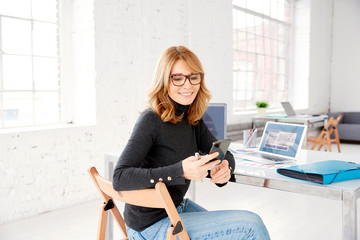 Portrait of mature businesswoman text messaging while sitting in the office and working