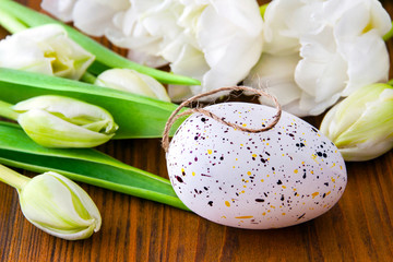 Easter egg decoration and tulips against wooden background