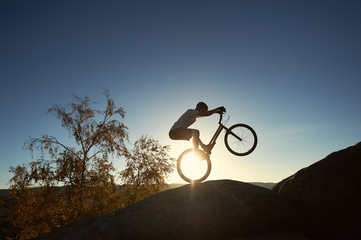 Silhouette of cyclist riding on back wheel on trial bike. Strong sportsman rider balancing on the edge of big rock on the top of mountain at sunset. Concept of extreme sport active lifestyle