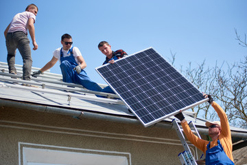 Male team workers installing stand-alone solar photovoltaic panel system. Four electricians lifting blue solar module on roof of modern house. Alternative energy innovation environmental concept.