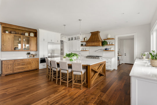 Beautiful Large Kitchen in New Home with Dark Hardwood Floors and Accents, and White Counters, Cabinets, and Backsplash
