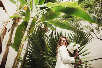 Young gorgeous woman in white jacket holding little bridal bouquet of flowers in hand dreamily looking in camera with big green leaves overhead in greenhouse