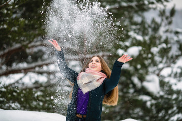 Beautiful girl playing with snow in an amazing winter.
