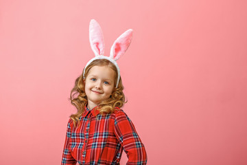 Portrait of a cute little child girl with bunny ears on a colored background. Happy easter