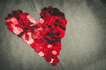 Red heart consists of small confetti on gray background