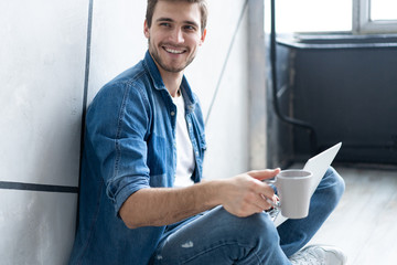 Young man sitting on floor with laptop and cup of coffee in room.