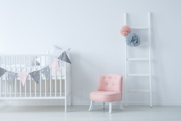 Elegant scandinavian kid's room with white wooden ladder with grey and pink pompons, crib with star shape pillows, and pastel pink armchair, copy space on empty white wall