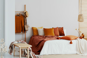 Bedroom with king size bed and brown and orange pillows