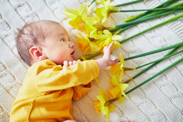 Newborn baby with bunch of yellow narcissus