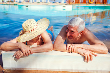 Senior couple relaxing in swimming pool. People enjoying vacation. Valentine's day