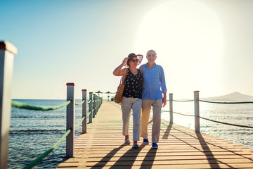 Senior couple walking on pier by Red sea. People enjoying vacation. Valentine's day