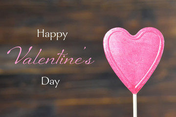 Valentines Day card. Heart candy lollipop on wooden background