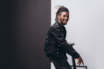 One attractive smiling black man in black jacket and black pants over gray background