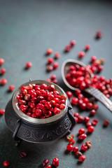 Pink pepper in vintage bowl on dark background. Closeup, selective focus