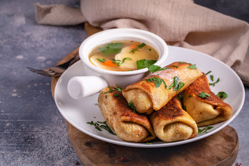 Homemade minced meat rolled crepes served with broth. Traditional Russian cuisine