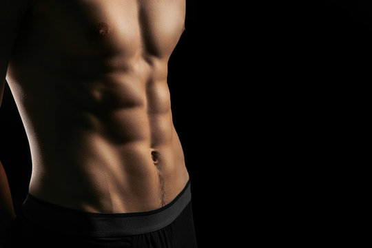 pumped handsome male press. Male athletic body closeup on black background