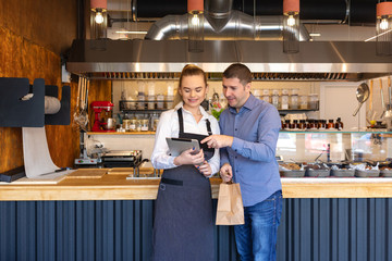 New fast food restaurant business owners using tablet for online orders -  home delivery concept