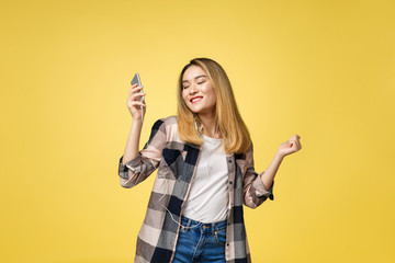 Fashion smiling asian woman listening to music in earphones over yellow background.