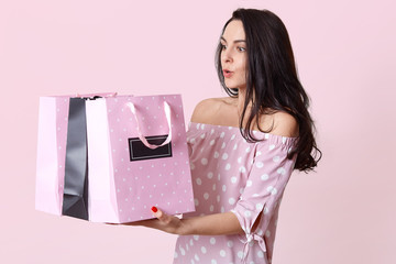 Shocked surprised European young woman holds bags, astonished to recieve many presents, dressed in polka dot dress, wants to open gift, poses against pink background. People and shopping concept