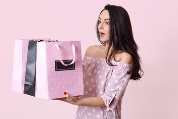 Studio shot of surprised brunette young lady has bated breath, holds many bags, returns from shop with many purchases, dressed in polka dot dress, isolated over rosy background. Shopping concept