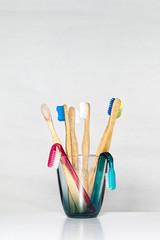 Zahnbürsten aus Bambus und Plastik in einem Zahnputzbecher isoliert auf einem weißen Hintergrund