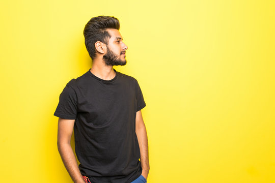 Indian bearded man standing isolated on yellow background