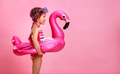 happy child girl in swimsuit with swimming ring flamingo on a colored pink background