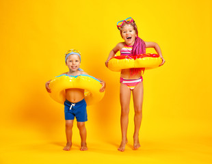 happy children girl and boy in swimsuit with swimming ring donut on colored yellow background.