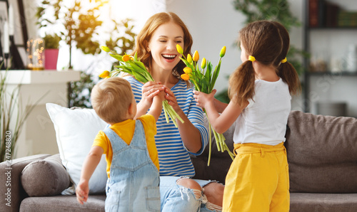 Happy mother's day! Children congratulates moms and gives her a gift and flowers