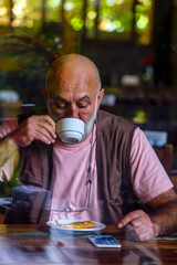 Olld man drinking coffee and using a cel phone