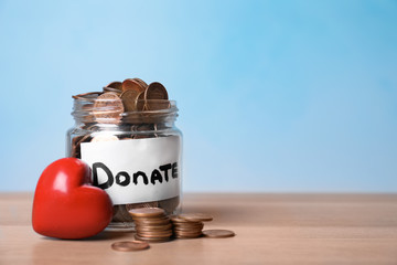Red heart and donation jar with money on table against color background. Space for text