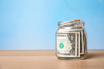 Donation jar with money on table against color background. Space for text