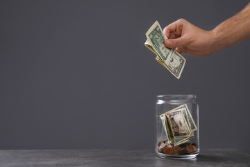 Man putting money into donation jar on table against grey background, closeup. Space for text