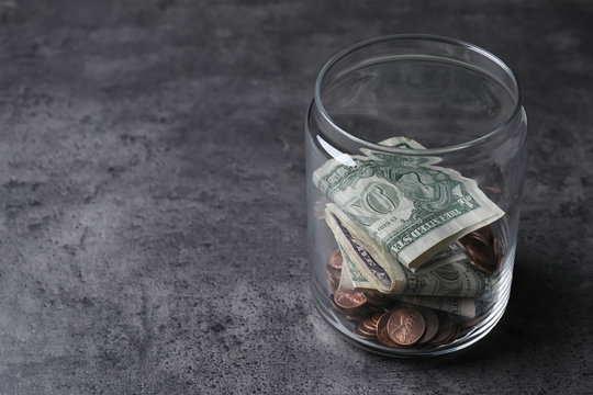 Donation jar with money on grey background. Space for text