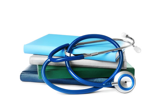 Stack of student textbooks and stethoscope on white background. Medical education