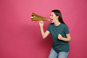 Emotional young woman with megaphone on color background