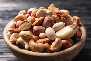 Bowl with organic mixed nuts on table, closeup