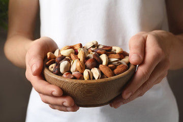 Woman holding bowl with organic mixed nuts, closeup