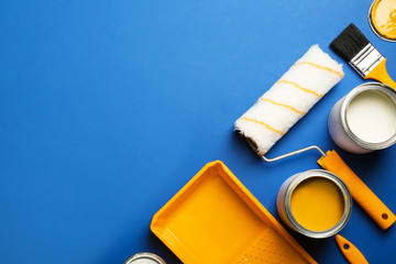 Flat lay composition with paint cans, decorator tools and space for text on color background