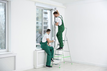 Construction workers installing plastic window in house