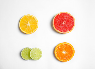Different citrus fruits on white background, top view