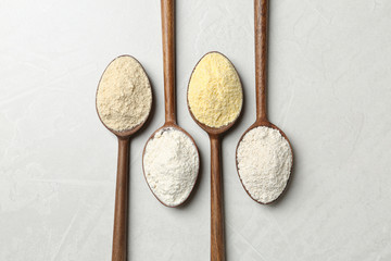 Spoons with different types of flour on table, top view